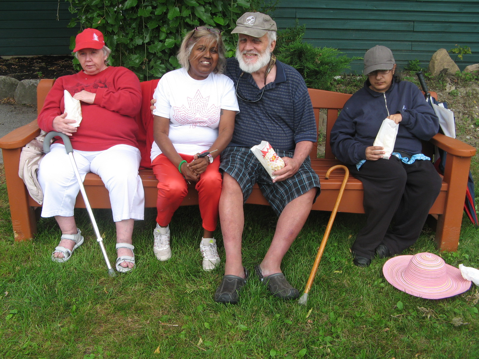 Four residents sitting on a bench eating popcorn