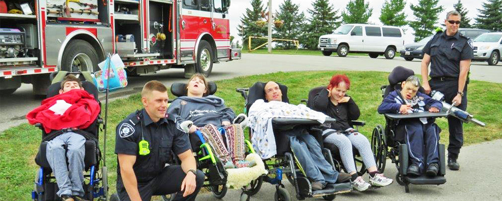 group of people in wheelchairs pose with firefighters